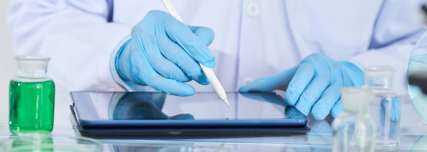 Close-up of chemist in protective glove using digital tablet in his work at lab