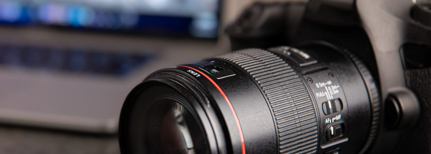 Professional camera on a blurred background with a laptop. The concept of working with photos and videos.
