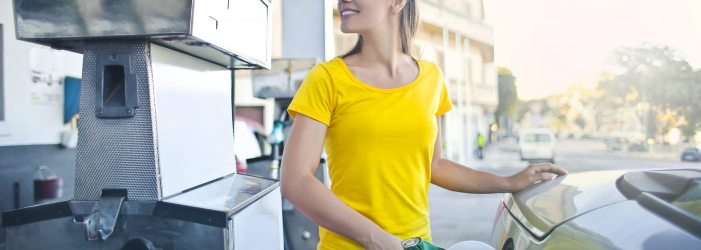 woman-in-yellow-shirt-while-filling-up-her-car-with-gasoline-3812750